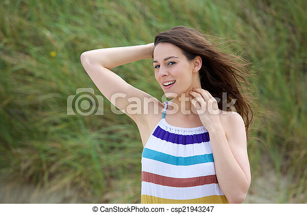 Attractive young woman smiling with hand in hair - csp21943247