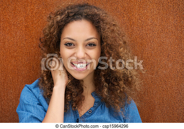 Attractive young woman smiling with hand in hair - csp15964296