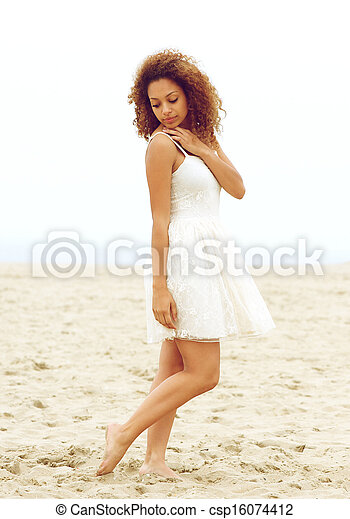 Attractive young woman walking alone on beach - csp16074412