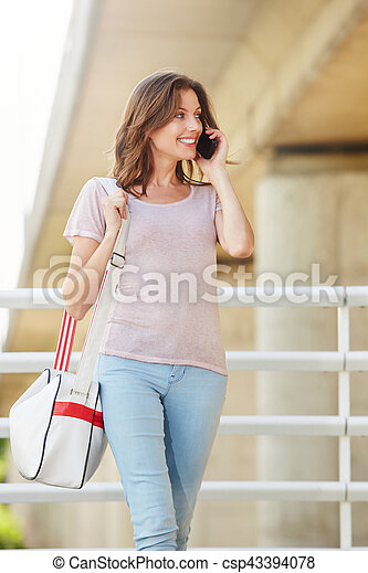 attractive young woman with bag talking on mobile phone - csp43394078