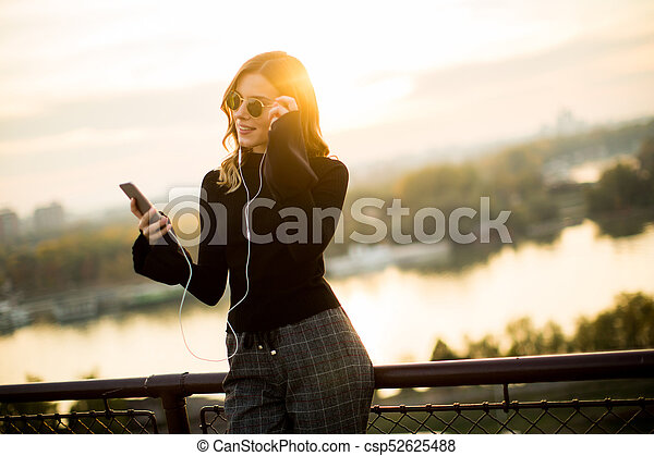 Attractive young woman with mobile phone outdoor - csp52625488