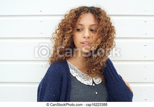 Attractive young woman with wind blowing hair across face - csp16223388