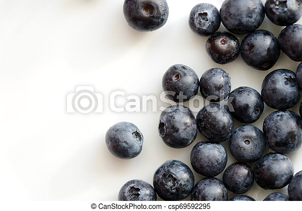 Frische Blaubeerbeeren auf einem weißen Teller. Top Aussicht - csp69592295
