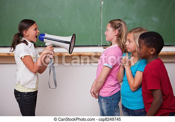Una colegiala enojada gritando a través de un megáfono a sus compañeros de clase - csp8249745