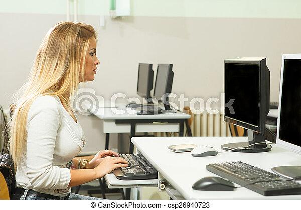 Una joven trabajando en una computadora en la clase - csp26940723