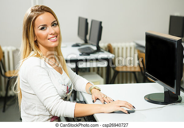 Una joven trabajando en una computadora en la clase - csp26940727