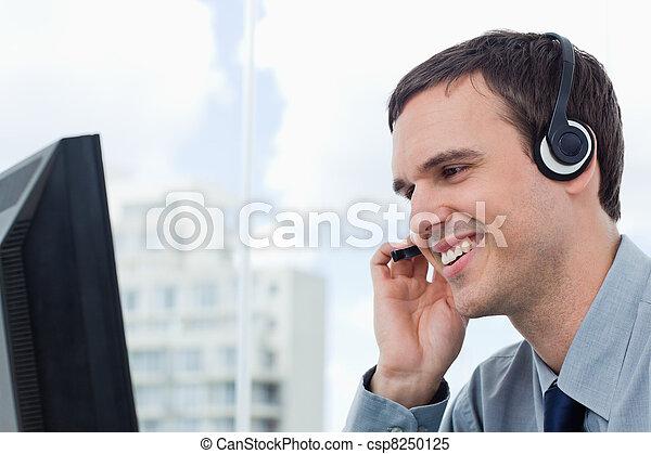 Un trabajador sonriente usando un auricular - csp8250125