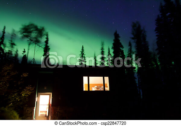 Aurora borealis above house in forest - csp22847720