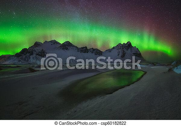 Aurora Borealis green reflection over the water at Stokksnes - csp60182822