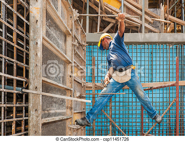 Authentic construction worker in a difficult balancing position between scaffold and formwork frame - csp11451726