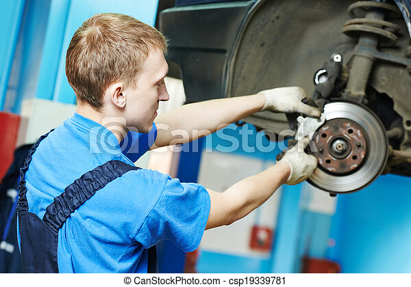 auto mechanic at car brake shoes replacement - csp19339781