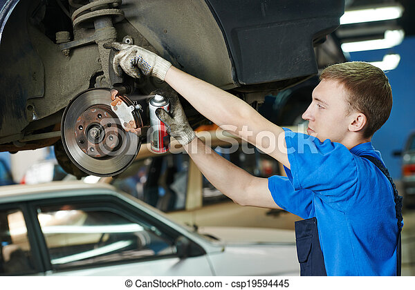 auto mechanic at car brake shoes replacement - csp19594445