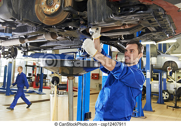 auto mechanic at car suspension repair work - csp12407911