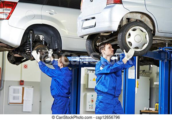 auto mechanic at car suspension repair work - csp12656796