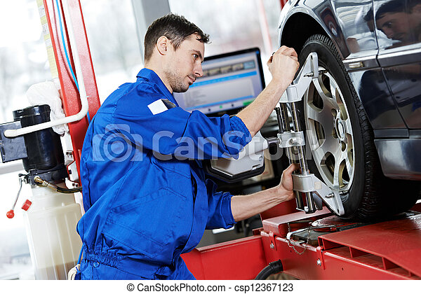 auto mechanic at wheel alignment work with spanner - csp12367123