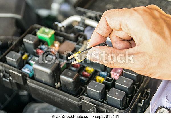 Auto mechanic checking a car fuse - csp37918441