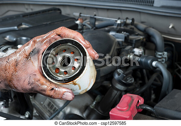 Auto mechanic holding oil filter - csp12597585
