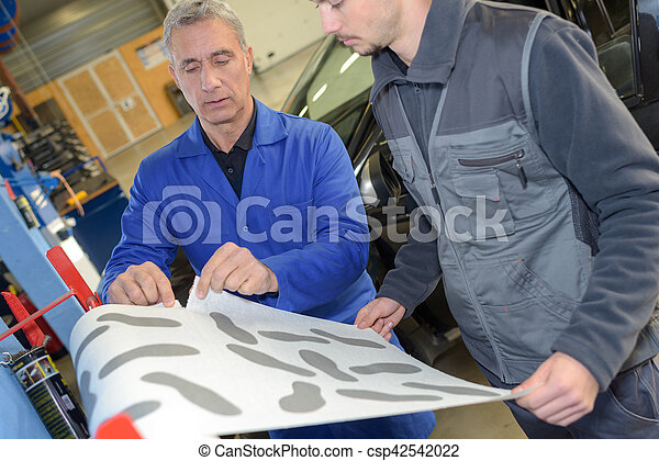 auto mechanic shows his trainee maintenance of the car - csp42542022