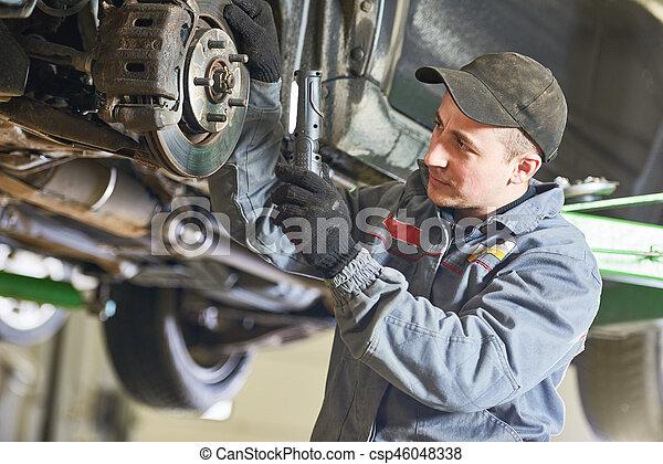 Auto repair service. Mechanic inspecting car suspension - csp46048338