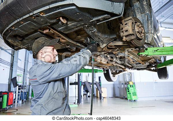 Auto repair service. Mechanic works with car suspension - csp46048343
