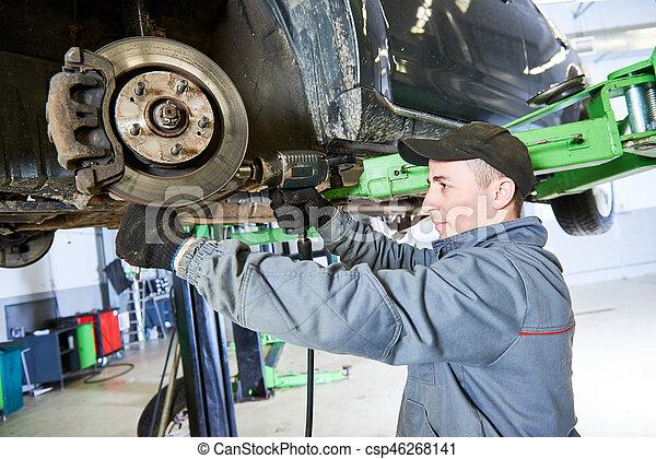 Auto repair service. Mechanic works with car suspension - csp46268141
