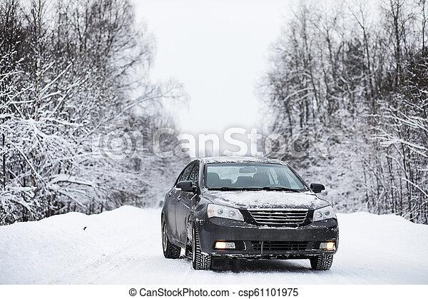 Das Auto steht auf einer verschneiten Straße - csp61101975
