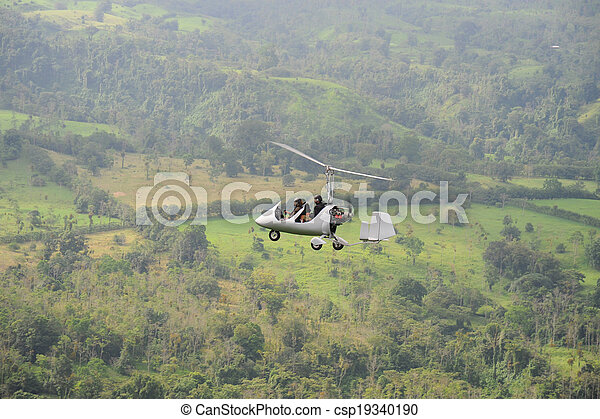 Autogyro flying above the tropical landscape - csp19340190