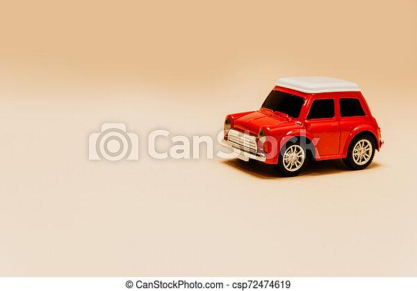 Coche rojo de juguete en un fondo beige plana con lugar para el texto - csp72474619