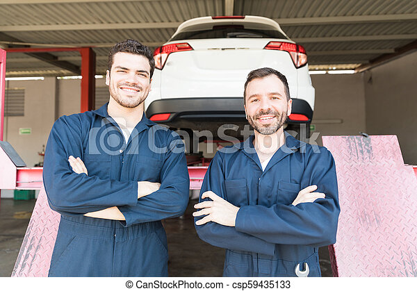 Automotive Workers Showing Contentment In Garage - csp59435133