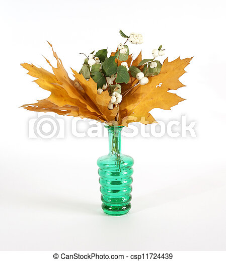 Autumn bouquet of oak leaves in a vase with colored glass on a white background - csp11724439