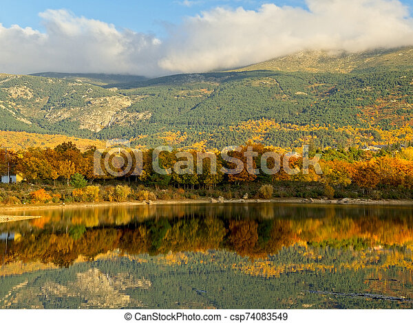 Autumn colors reflected in the lake at sunset - csp74083549