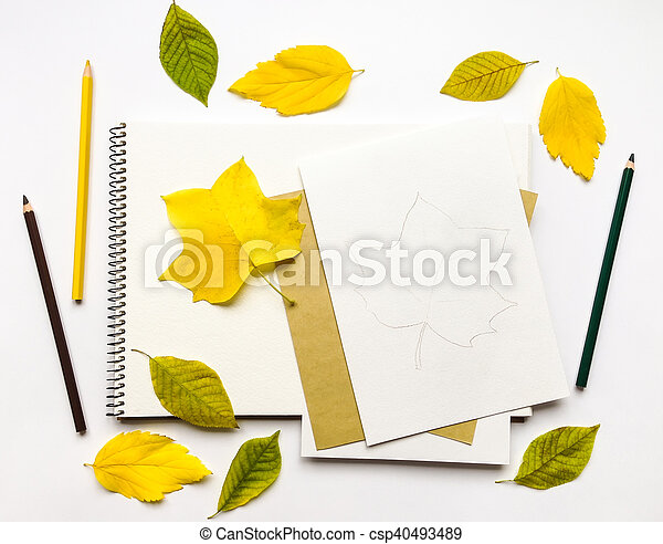 Autumn composition with album and pencils, decorated with yellow and green leaves. Flat lay, top view - csp40493489