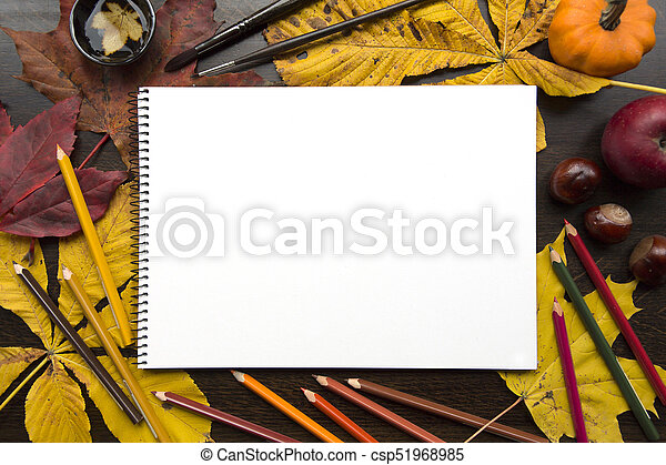 Autumn composition with empty album and fallen leaves - csp51968985