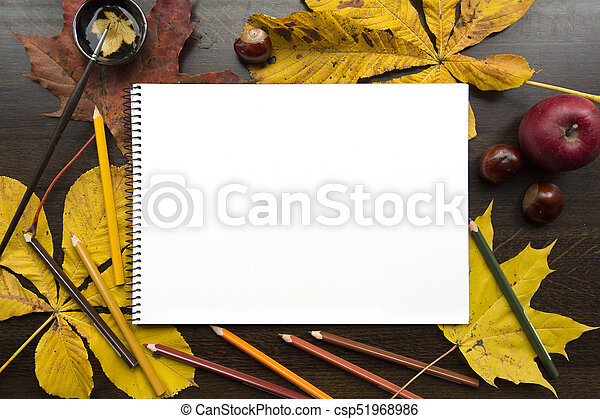 Autumn composition with empty album and fallen leaves - csp51968986