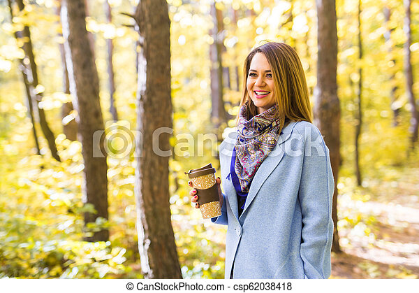 Autumn, drinks and people concept - Woman holding cup of hot drink - csp62038418