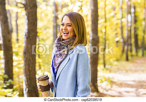 Autumn, drinks and people concept - Woman holding cup of hot drink - csp62038519