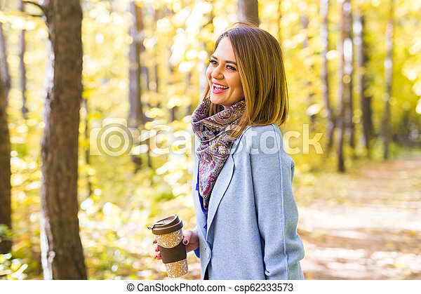 Autumn, drinks and people concept - Woman holding cup of hot drink - csp62333573