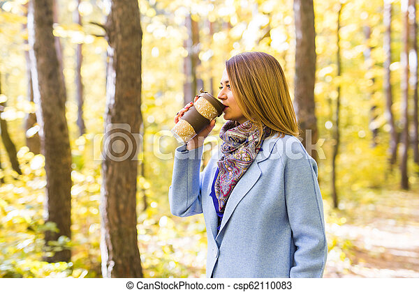 Autumn, drinks and people concept - Woman holding cup of hot drink - csp62110083