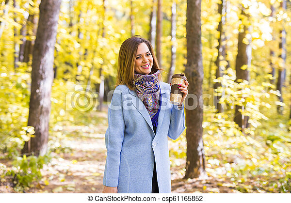 Autumn, drinks and people concept - Woman holding cup of hot drink - csp61165852