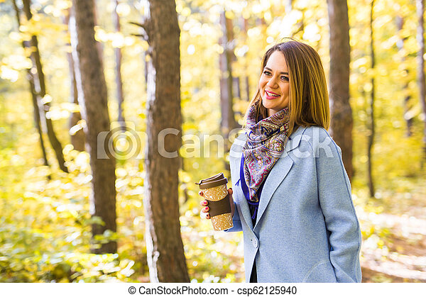 Autumn, drinks and people concept - Woman holding cup of hot drink - csp62125940
