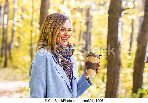 Autumn, drinks and people concept - Woman holding cup of hot drink - csp62141996