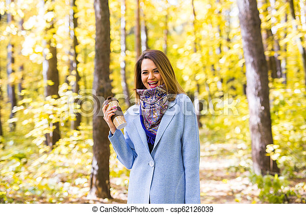 Autumn, drinks and people concept - Woman holding cup of hot drink - csp62126039