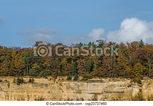 autumn forest and sandstone cliff - csp23737460