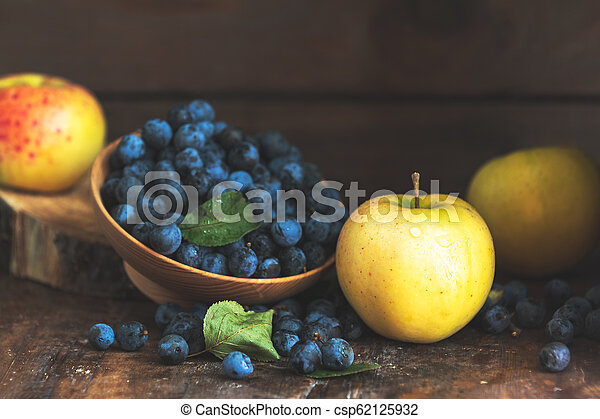 Autumn harvest blue sloe berries and apples on a wooden table background. Copy space. Dark rustic style. Natural remedy - csp62125932