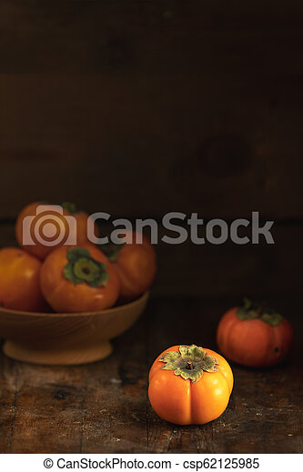 Autumn harvest Persimmon fruits in bowl on a wooden table background. Copy space. Dark rustic style. Natural remedy - csp62125985