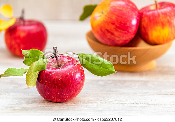 Autumn harvest red apples fruits on a light gray wooden table background. - csp63207012