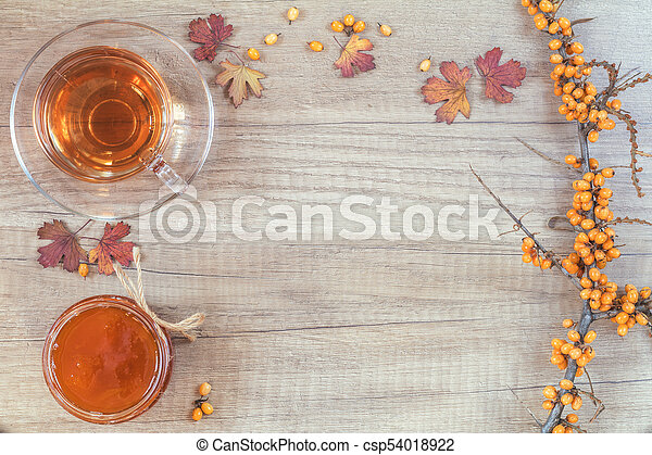 Autumn healthy hot drink concept. Branch of common sea buckthorn with berry, cup of tea, jar of jam on light wooden background. Toned photo with copy space. - csp54018922