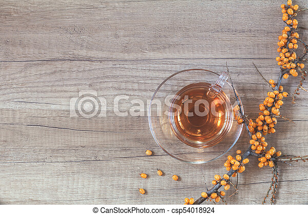 Autumn healthy hot drink concept. Branch of common sea buckthorn with berry, cup of tea, on light wooden background. Toned photo with copy space. - csp54018924