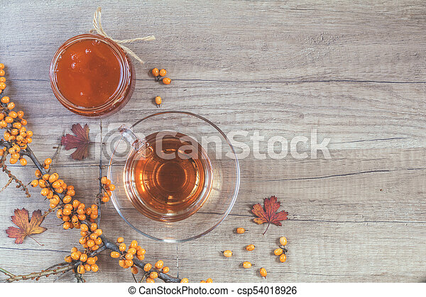 Autumn healthy hot drink concept. Branch of common sea buckthorn with berry, cup of tea, jar of jam on light wooden background. Toned photo with copy space. - csp54018926