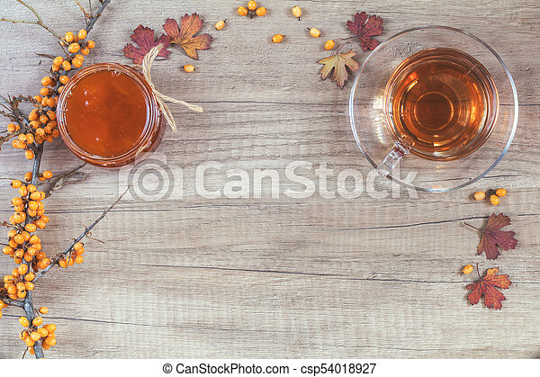 Autumn healthy hot drink concept. Branch of common sea buckthorn with berry, cup of tea, jar of jam on light wooden background. Toned photo with copy space. - csp54018927